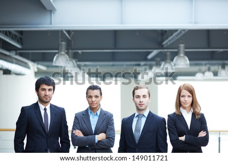 Group of confident businesspeople in suits standing in line - stock photo
