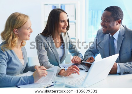 Group of confident businesspeople interacting at meeting