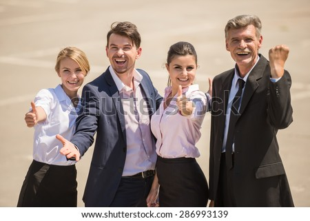 Group of confident smiling business people enjoying their success.