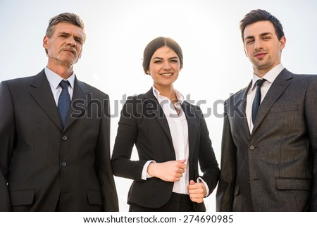 Group of confident successful businesspeople in suits at a meeting  standing on white background. - stock photo