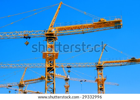 Group of construction cranes against clear blue sky - stock photo