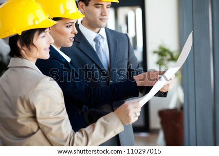 group of construction managers looking at blue print - stock photo