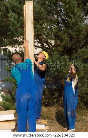 Group of construction workers aligning a prefab wooden wall panel on a new build house - stock photo