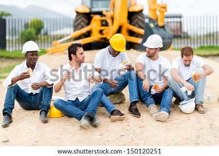 Group of construction workers on a break at a building site - stock photo