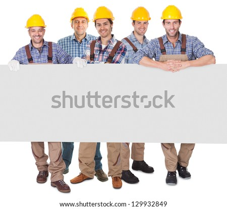 Group of construction workers presenting empty banner. Isolated on white