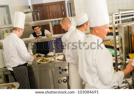 Group of cooks in professional kitchen prepare meals restaurant service - stock photo