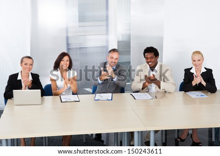 Group Of Corporate Personnel Officers Applauding In Office - stock photo