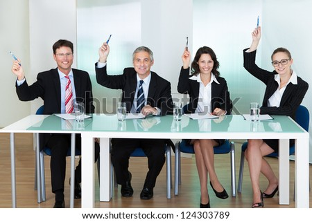 Group of corporate recruitment officers interviewing for a professional vacancy raising their pens - stock photo