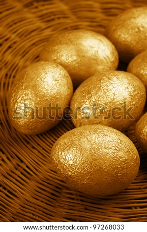 Group of crackle golden Easter eggs in wicker basket. - stock photo