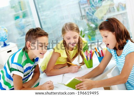 Group of curious classmates looking at note in notebook in girl hands at workplace - stock photo