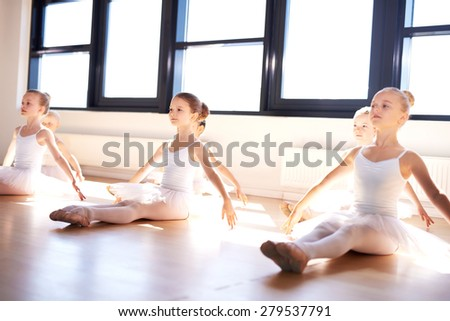 Group of cute graceful little ballerinas in class sitting on the wooden floor of the studio practising a pose with outstretched arms in front of bright windows - stock photo