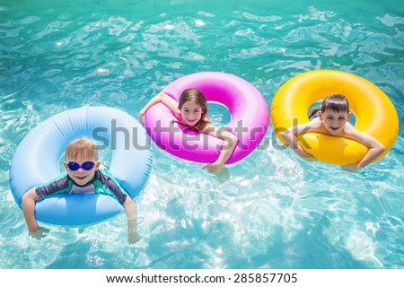 Group of cute kids playing on inflatable tubes in a swimming pool on a sunny day - stock photo