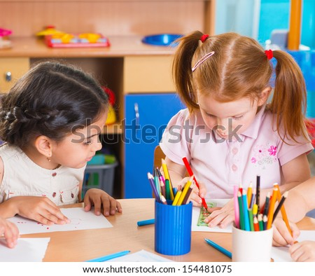 Group of cute little preschool kids drawing with colorful pencils - stock photo