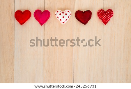 Group of cute red tone hearts handmade crafts from cotton and silk cloth place in line on wood with space background, love and wedding symbol - stock photo