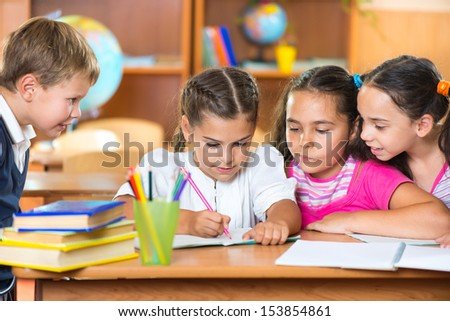 Group of cute schoolchildren drawing and having fun in classroom - stock photo