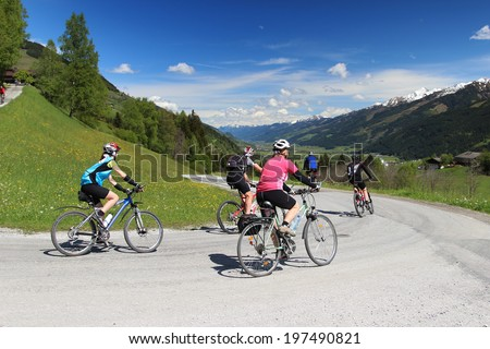 Group of cyclists descended the hill in Austrian Alps - stock photo