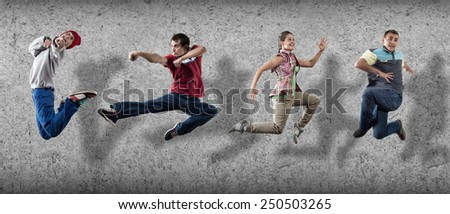 Group of dancer in jump on cement background - stock photo