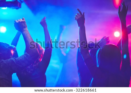 Group of dancing people with raised arms enjoying disco party
