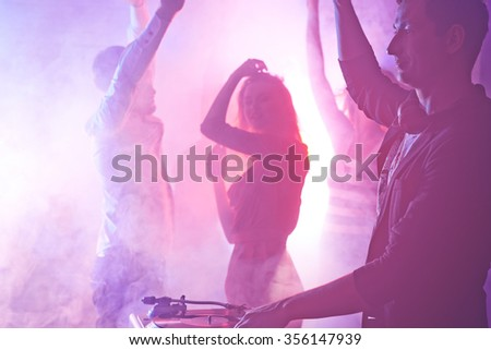 Group of dancing young people enjoying in night club - stock photo
