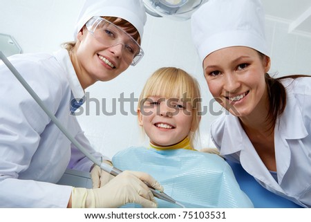 Group of dentist, assistant and little girl looking at camera - stock photo