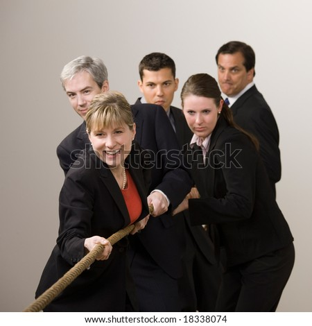 Group of determined co-workers pulling rope in tug-of-war - stock photo