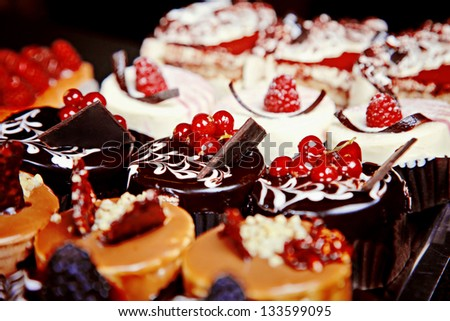 Group of different mini cakes berries and chocolate - stock photo