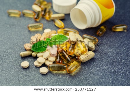 Group of different pills and multivitamins on a dark background - stock photo