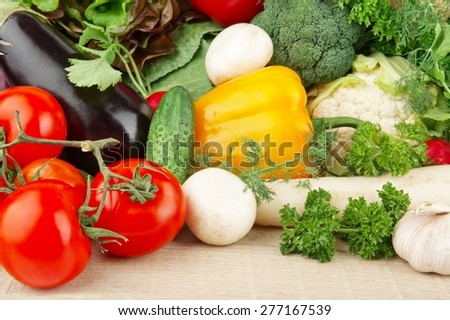 Group of different vegetables on wooden plank - stock photo