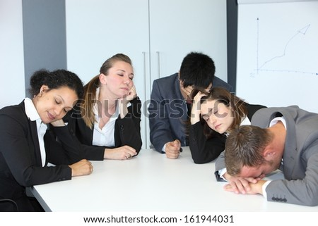 Group of diverse bored demotivated businesspeople in a meeting seated at a table n the office napping with their eyes close slouching on the table - stock photo