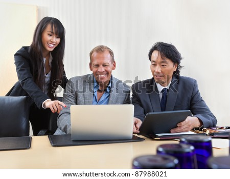 Group of diverse colleagues working on laptop - stock photo