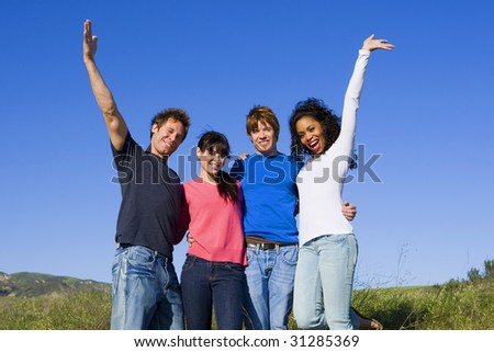 Group of diverse friends playing on a bright sunny day - stock photo