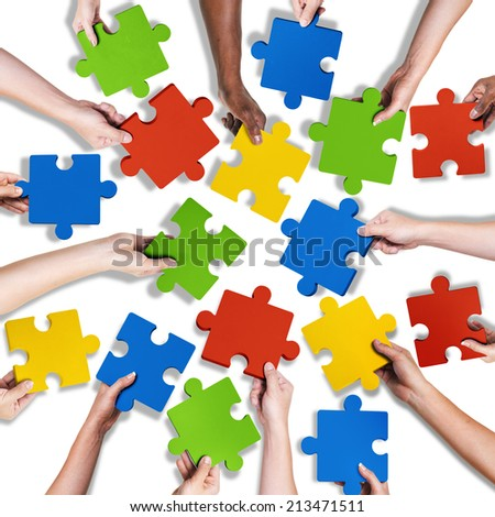 Group of Diverse Hands Holding Jigsaw Puzzle - stock photo