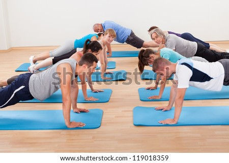Group of diverse healthy people in a gym class doing press ups while exercising on two rows of blue mats on a wooden floor