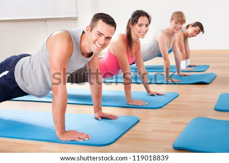 Group of diverse healthy people in a gym class doing press ups while exercising on two rows of blue mats on a wooden floor - stock photo