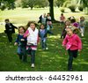 group of diverse kids running outside in fall - stock