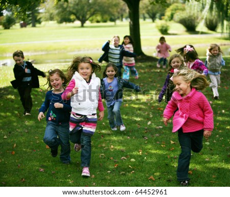 group of diverse kids running outside in fall
