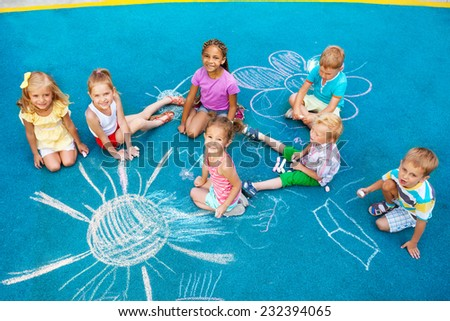 Group of diverse looking boys and girls drawing with chalk on colorful playground sitting together  - stock photo