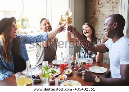 Group of diverse male and female laughing young adults putting their drinking glasses together at table in restaurant with large window - stock photo