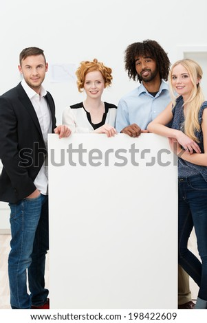 Group of diverse multiehnic young businesspeople with a blank white sign with copyspace for your advertising, text or announcement - stock photo