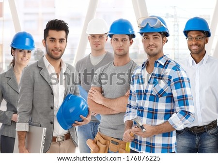 Group of diverse people from building industry: architects, managers, workers posing together for a team portrait. - stock photo