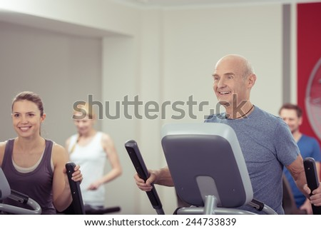 Group of diverse people working out together at the gym with focus to a smiling young woman and fit senior man in the foreground in a health and fitness concept - stock photo
