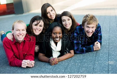 Group of diverse students outside smiling in a pyramid - stock photo