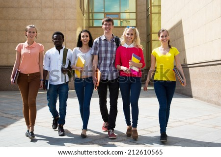 Group of diverse students outside walking together - stock photo
