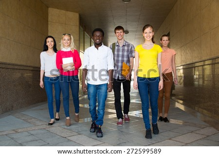 Group of diverse students outside walkling together - stock photo