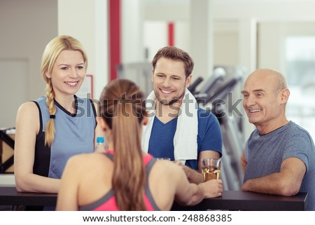 Group of diverse young and old friends relaxing after a workout at the gym being served drinks at the in house bar