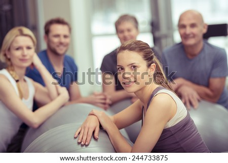 Group of diverse young and old people in a pilates class at the gym with focus to an attractive young woman in the foreground in a health and fitness concept