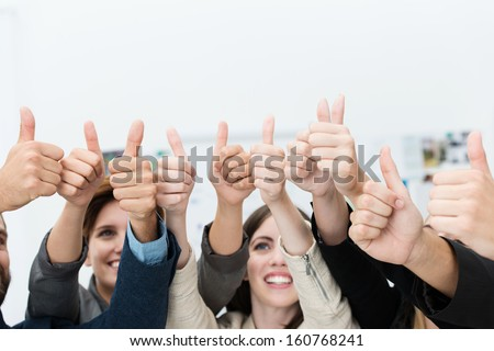 Group of diverse young businesspeople giving a simultaneous thumbs up gesture of approval, agreement or success, or to show their support and motivation - stock photo