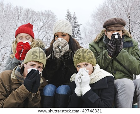 Group of diverse young friends blowing noses outdoors in winter