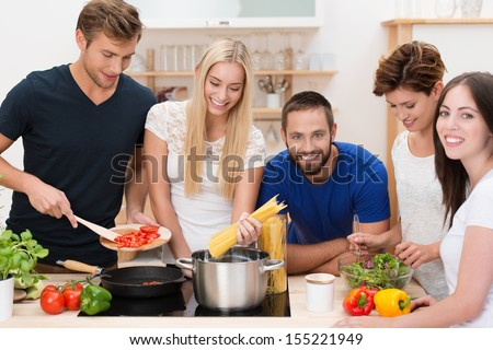 Group of diverse young friends preparing pasta standing around the stove cooking spaghetti and a tomato based sauce - stock photo