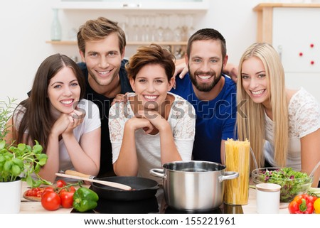 Group of diverse young people posing together in the kitchen while preparing pasta with an array of fresh ingredients and spaghetti in front of them as they smile at the camera - stock photo